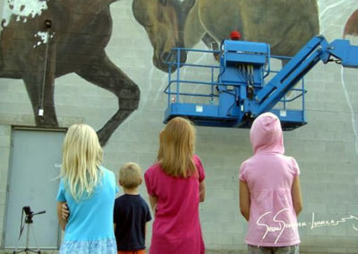 Children watching Susan paint giant horses