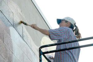 Susan working hard painting a giant Ozarks water ways mural