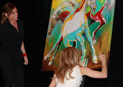 Sheryl Crow signs Susan's painting on stage during concert